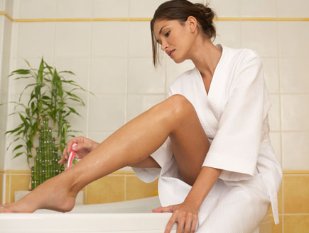 בחורה בחלוק לבן מגלחת את רגליה באמבט