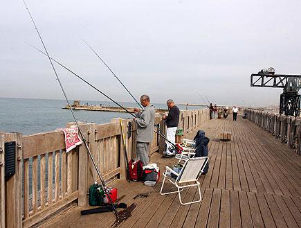 דייגים על שביל עץ בנמל תל אביב ומשמאל מזח והים (צילום: עודד קרני)
