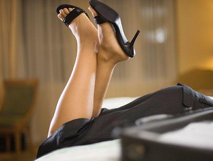 נעלי סטילטו שחורות רגליים מקופלות על המיטה (צילום: jupiter images)