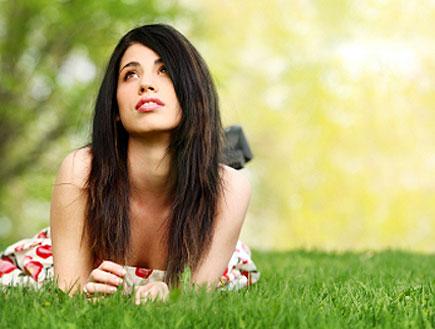 בחורה שוכבת על דשא ומביטה למעלה (צילום: Lise Gagne, Istock)