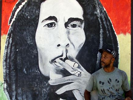 אדם יושב ומאחוריו ציור של בוב מרלי (צילום: Reuters)