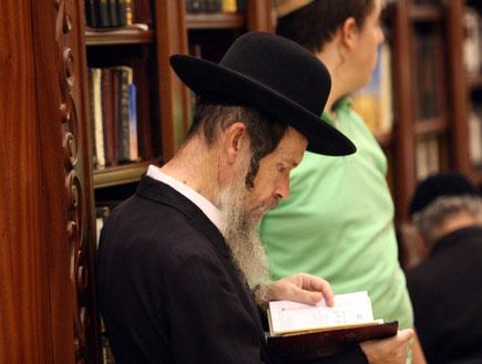 איש דתי חרדי קורא בספר מאחוריו איש בירוק (צילום: מערכת MAKO 5)