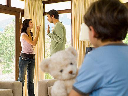 ילד עם דובי מסתכל עם גבר ואישה מתווכחים ליד חלונות (צילום: אור גץ, jupiter images)