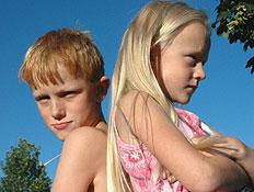 ילדה בורוד וילד בלי חולצה עומדים זועפים גב אל גב ל