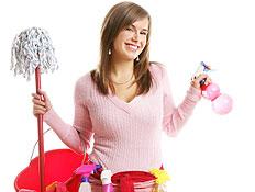 בחורה בורוד מחייכת עם סינר אדום וחומרי ניקוי מחזיק (צילום: lisegagne, Istock)