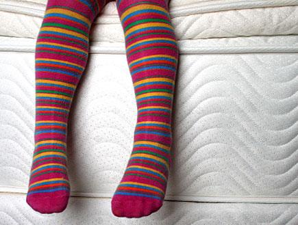 רגלי ילדה עם גרבוני פסים על מזרן לבן של מיטה (צילום: Lisa Swanson, Istock)