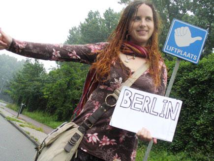 בחורה עוצרת טרמפים אוחזת שלט לברלין (צילום: סתיו שפיר)