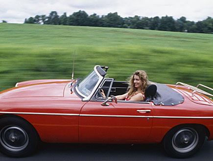 בחורה במכונית ספורט עם גג פתוח