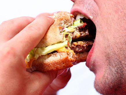 גבר אוכל המבורגר (צילום: istockphoto)