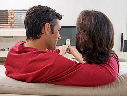 זוג מחזיק שלט מול טלוויזיה (צילום: jupiter images)