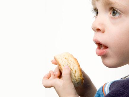 פרופיל של ילד קטן בפה פתוח מחזיק לחם (צילום: Leslie Banks, Istock)
