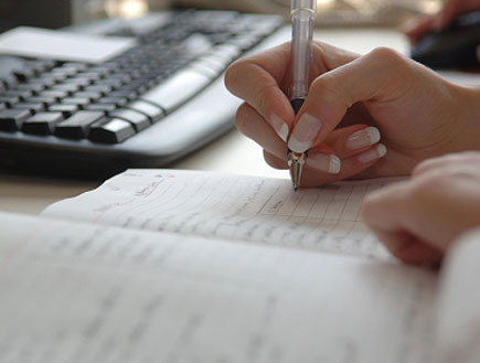 יד של אישה,בציפורניים יפות, מחזיקה עט ליד מקלדת (צילום: webphotographeer, Istock)