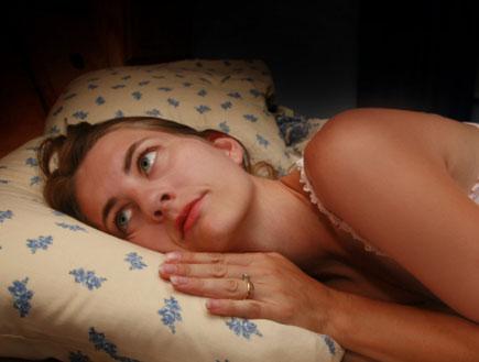 אישה שוכבת על כרית בעיניים פקוחות (צילום: Sharon Dominick, Istock)