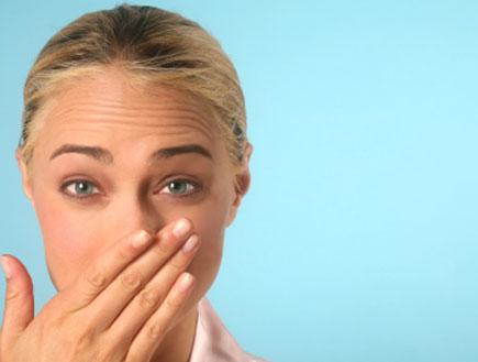 אישה מחזיקה יד על הפה-ריח רע (צילום: hanzl, Istock)