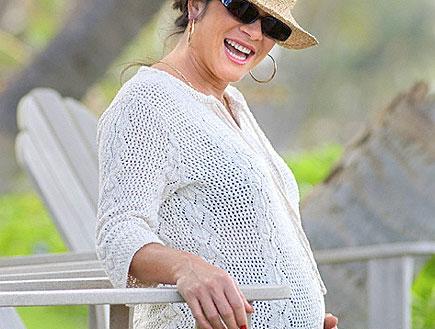 אישה מבוגרת מחייכת בהריון בג'ינס על כיסא לבן בגינה (צילום: jupiter images)