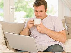 גבר בלבן יושב עם מחשב נישא עליו וספל בסלון מאחוריו (צילום: jupiter images)