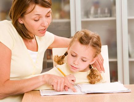 אישה יושבת עם ילדה ומלמדת אותה בשולחן עץ (צילום: jupiter images)