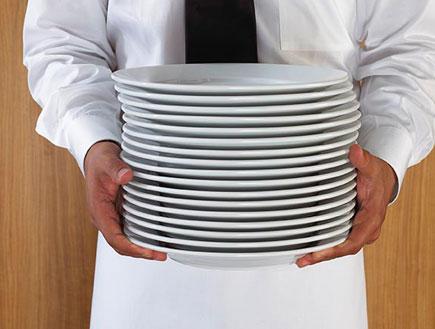 מלצר מחזיק ערימת צלחות (צילום: jupiter images)