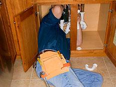 שרברב בג'ינס שוכב מתחת ומתקן כיור עם כלים