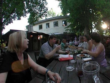 אנשים יושבים לאורך שולחן עץ בטברנה וינאית (צילום: אור גץ)