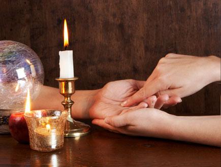 קריאה בכף יד, בצד כדור בדולח ונרות (צילום: אור גץ)