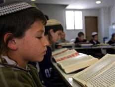 """ילד עם כיפה מול ספר תנ""""ך פתוח"""