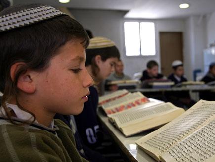"""ילד עם כיפה מול ספר תנ""""ך פתוח (צילום: Reuters)"""