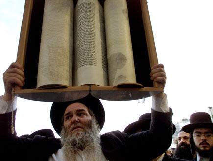 דתי מחזיק ספר תורה גדול (צילום: Reuters)
