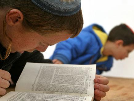 ילד ג'ינג'י עם כיפה קורא בספר מקרוב (צילום: Reuters)