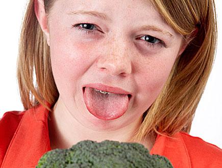ילדה עם נמשים וטבעות בשיניים מוציאה לשון מעל ברוקו (צילום: jupiter images)