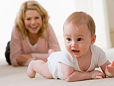תינוק בלבן זוחל ומאחוריו אימו מחייכת בורוד (צילום: jupiter images)