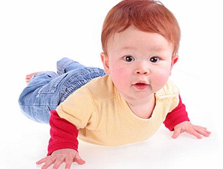 תינוק ג'ינג'י באדום צהוב זוחל על הבטן (צילום: Nghe Tran, Istock)