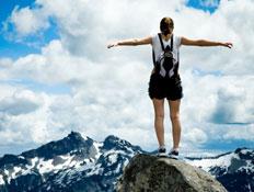 חופש - אישה עומדת על פסגת הר ופורשת ידיים לצדדים (צילום: iStock)