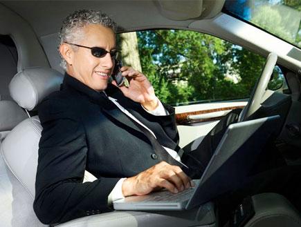 איש עסקים עם מחשב נייד מדבר בנייד במכונית