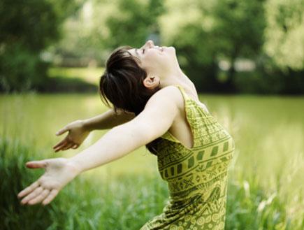 יציאה לחופשה - אישה בשמלה ירוקה בשדה ירוק (צילום: iStock)