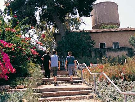 מדרגות שמובילות לבית ישן בגדרה כשברקע מגדל מים (צילום: ברוך גיאן)