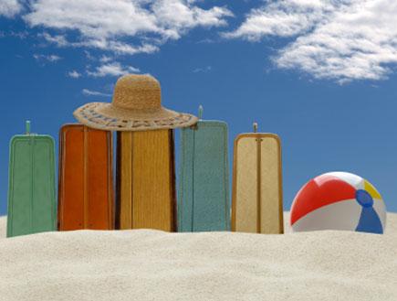 חופשת קיץ - מזוודות, כדור וכובע על חוף הים (צילום: iStock)