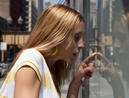בחורה בקניות בוחנת חלון ראווה (צילום: iStock)
