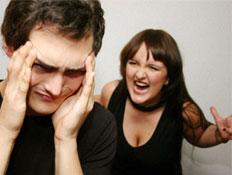אישה צועקת על גבר שמחזיק את הראש