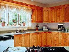 מטבח מאובזר מעץ עם חלון, וילונות ופרחים