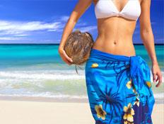 אישה בבגד ים מחזיקה קוקוס ומאחוריה הים (צילום: אור גץ)