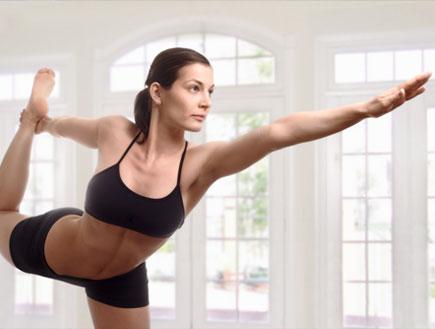 אשה עושה יוגה, מחזיקה רגל ומושיטה יד (צילום: istockphoto)