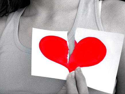 אדם מחזיק לב אדום קרוע על דף (צילום: אור גץ)