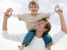 גבר מרים ילד בלונדיני על הכתפיים ומסתכל עליו על חו (צילום: jupiter images)