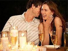 בחור לוחש באוזן בחורה צוחקת יושבים לשולחן עם נרות (צילום: jupiter images)