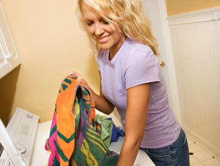 בחורה בסגול מחייכת ושמה בגדים במכונת כביסה (צילום: jupiter images)