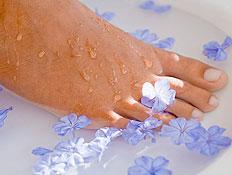 כף רגל נשית במים עם פרחים כחולים (צילום: jupiter images)
