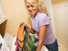 בחורה בסגול מחייכת ושמה בגדים במכונת כביסה