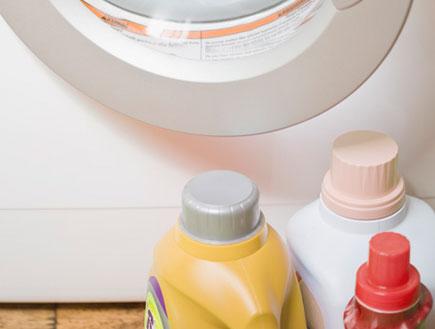 בקבוקי נוזל לכביסה ליד פתח של מכונת כביסה לבנה (צילום: jupiter images)