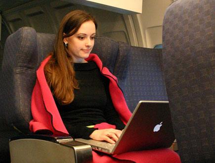 בחורה עם לפטופ מכוסה בשמיכה אדומה במטוס